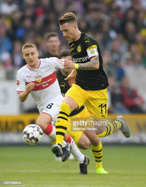 Marco Reus of Borussia Dortmund is challenged by Santiago Ascacibar of VfB Stuttgart during the Bundesliga match between VfB Stuttgart and Borussia...