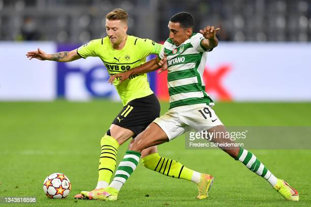 Marco Reus of Borussia Dortmund is challenged by Tiago Tomas of Sporting CP during the UEFA Champions League group C match between Borussia Dortmund...