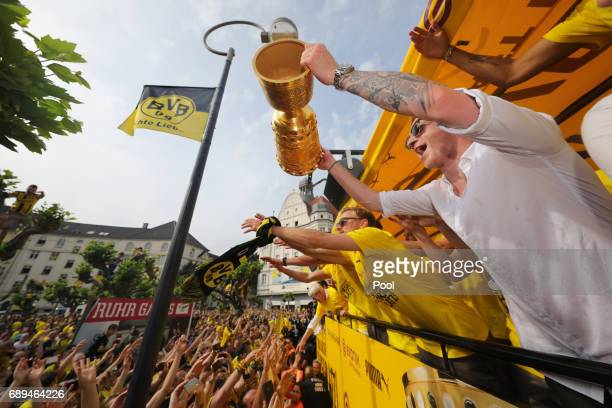 Marco Reus of Borussia Dortmund lifts the DFB Cup trophy as the team celebrates during a winner's parade at Borsigplatz on May 28 2017 in Dortmund...