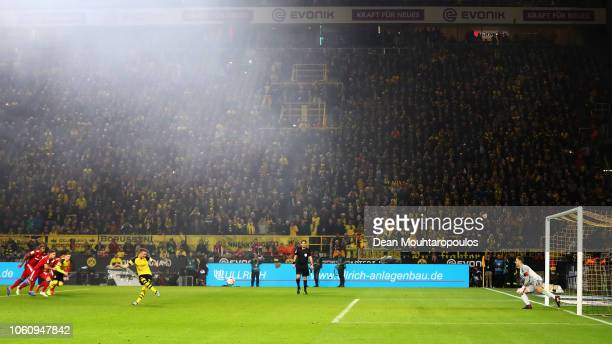 Marco Reus of Borussia Dortmund scores his team's first goal past Manuel Neuer of Bayern Munich from the penalty spot during the Bundesliga match...