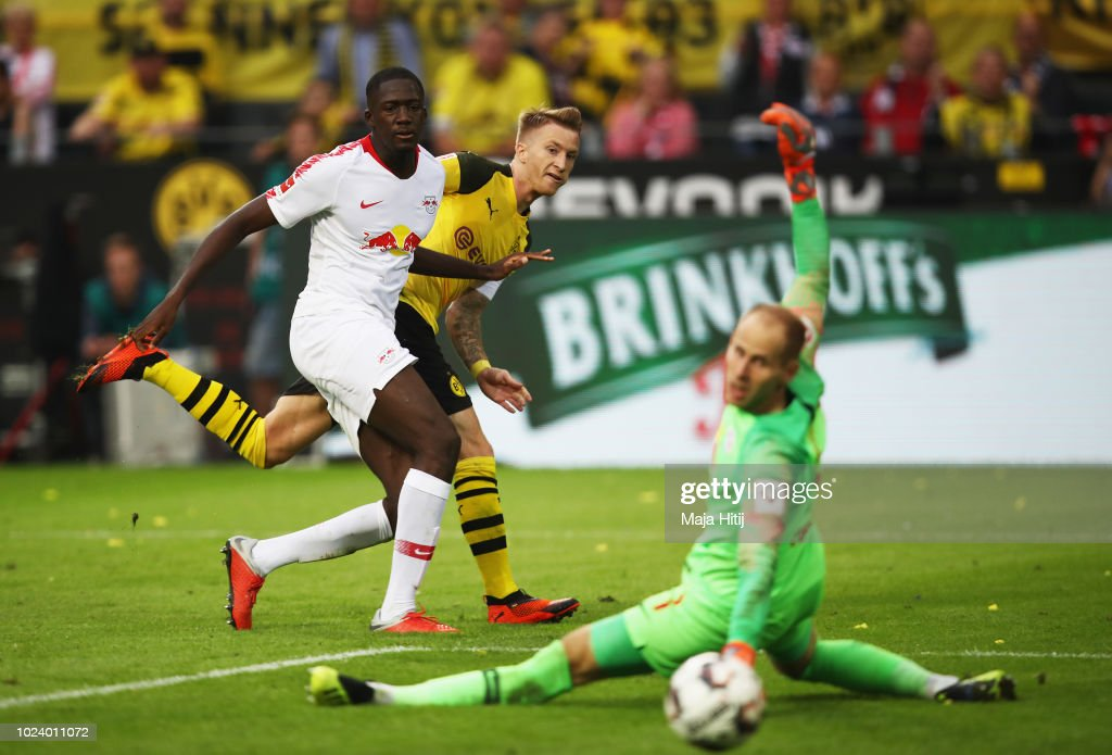 Marco Reus of Borussia Dortmund scores his team's fourth goal past Peter Gulacsi of RB Leipzig during the Bundesliga match between Borussia Dortmund and RB Leipzig at Signal Iduna Park on August 26, 2018 in Dortmund, Germany.