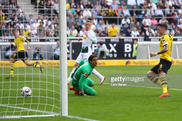 Marco Reus of Borussia Dortmund scores his team's second goal past Yann Sommer of Borussia Monchengladbach during the Bundesliga match between...