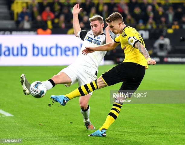 Marco Reus of Borussia Dortmund shoots on goal in front of Laurent Jans of Sport-Club Paderborn during the Bundesliga match between Borussia Dortmund...