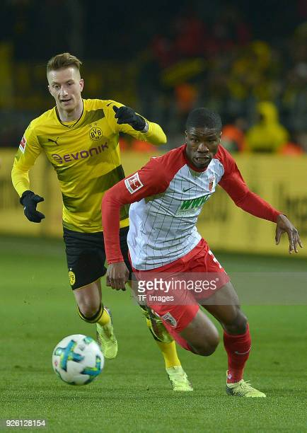 Marco Reus of Dortmund and Kevin Danso of Augsburg battle for the ball during the German Bundesliga match between Borussia Dortmund v FC Augsburg at...