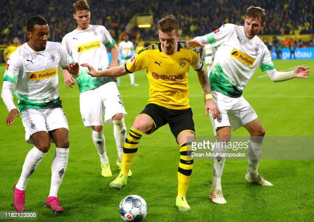 Marco Reus of Dortmund battles for the ball with Alassane Plea, Nico Elvedi and Christoph Kramer of Borussia Monchengladbach during the Bundesliga...