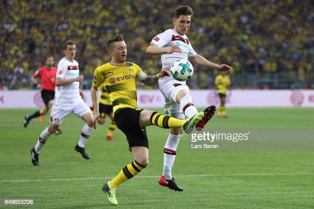 Marco Reus of Dortmund fights for the ball with Panagiotis Retsos of Leverkusen during the Bundesliga match between Borussia Dortmund and Bayer 04...