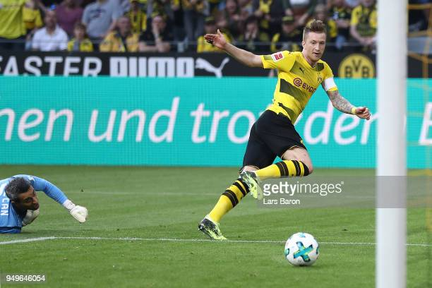 Marco Reus of Dortmund goes past goalkeeper Ramazan Oezcan of Bayer Leverkusen to score a goal to make it 20 during the Bundesliga match between...