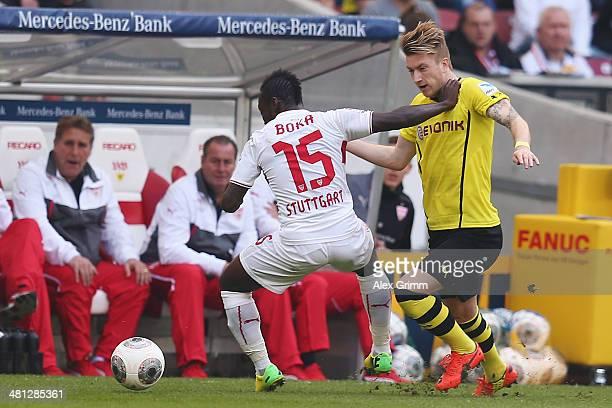 Marco Reus of Dortmund is challenged by Arthur Boka of Stuttgart during the Bundesliga match between VfB Stuttgart and Borussia Dortmund at...