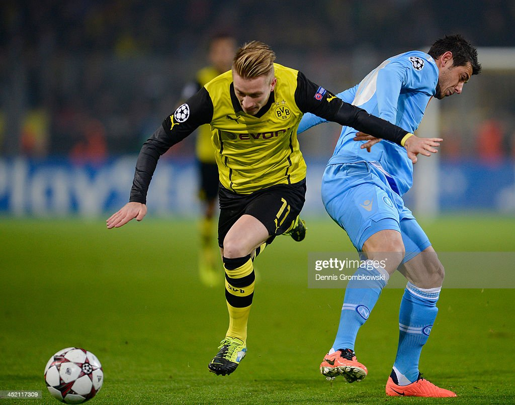 Marco Reus of Dortmund is challenged by Blerim Dzemaili of SSC Napoli during the UEFA Champions League Group F match between Borussia Dortmund and SSC Napoli at Signal Iduna Park on November 26, 2013 in Dortmund, Germany.