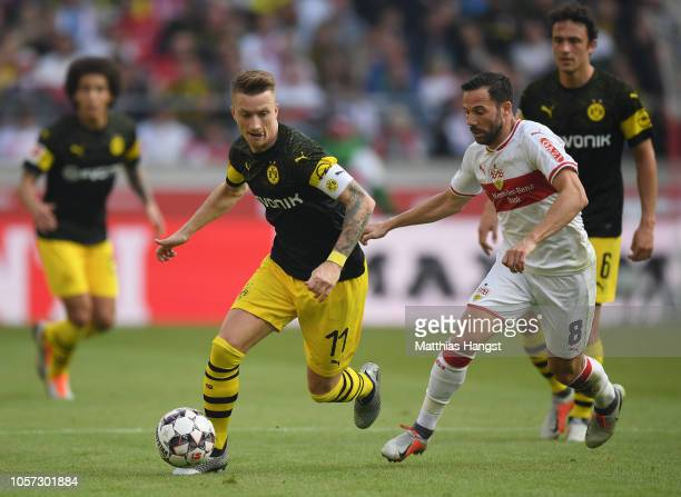 Marco Reus of Dortmund is challenged by Gonzalo Castro of Stuttgart during the Bundesliga match between VfB Stuttgart and Borussia Dortmund at...