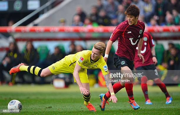 Marco Reus of Dortmund is challenged by Hiroki Sakai of Hannover during the Bundesliga match between Hannover 96 and Borussia Dortmund at HDI-Arena...