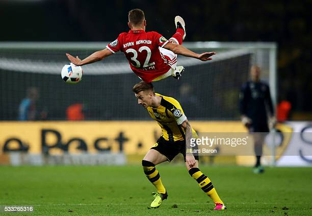 Marco Reus of Dortmund is challenged by Joshua Kimmich of Bayern during the DFB Cup Final between Bayern Muenchen and Borussia Dortmund at...