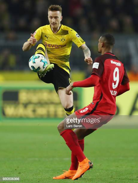 Marco Reus of Dortmund is challenged by Sebastian Haller of Frankfurt during the Bundesliga match between Borussia Dortmund and Eintracht Frankfurt...