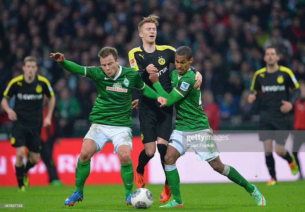 Marco Reus of Dortmund is challenged by Theodor Gebre Selassie and Philipp Bargfrede of Bremen during the Bundesliga match between Werder Bremen and Borussia Dortmund at Weserstadion on February 8, 2014 in Bremen, Germany.