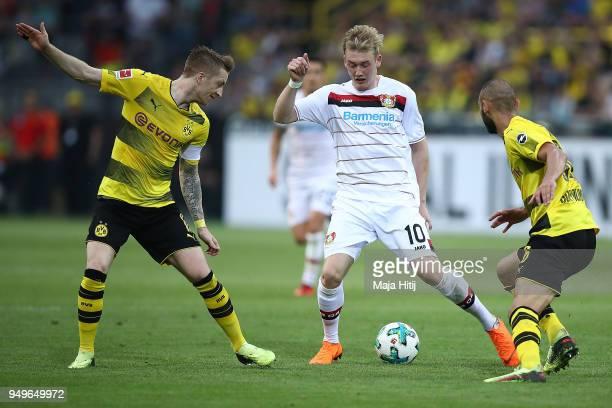 Marco Reus of Dortmund Julian Brandt of Bayer Leverkusen and Oemer Toprak of Dortmund fight for the ball during the Bundesliga match between Borussia...