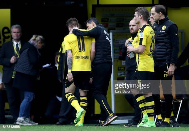 Marco Reus of Dortmund leaves injured the pitch next to head coach Thomas Tuchel during the Bundesliga match between Borussia Dortmund and Bayer 04...