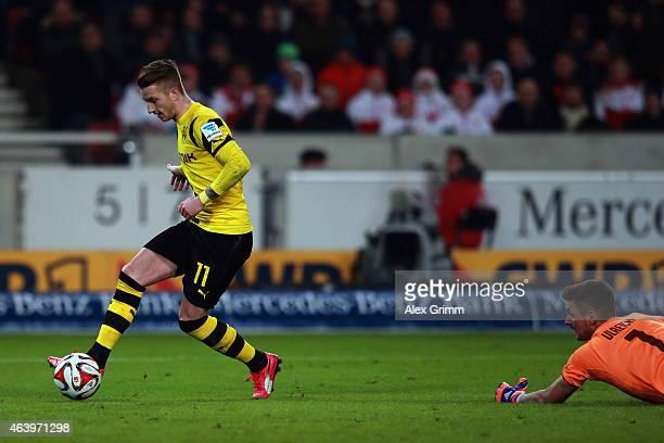 Marco Reus of Dortmund scores his team's third goal against goalkeeper Sven Ulreich of Stuttgart during the Bundesliga match between VfB Stuttgart...