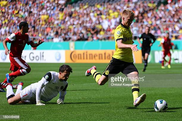 Marco Reus of Dortmund scores the first goal against Milos Mandic of Oberneuland during the first round DFB Cup match between FC Oberneuland and...