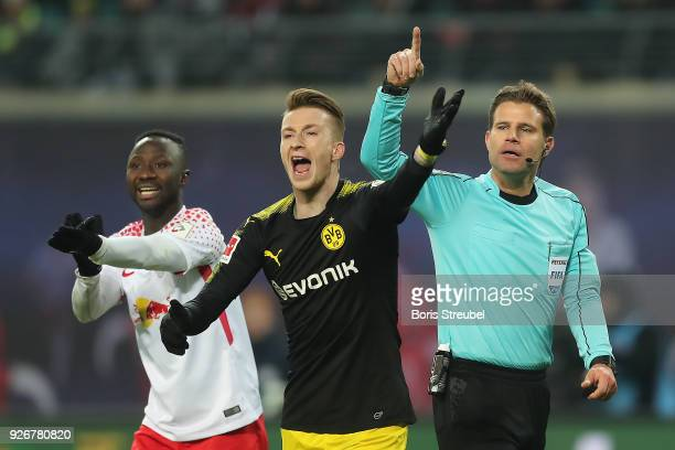 Marco Reus of Dortmund screams and referee Felix Brych and Naby Keita of Leipzig gesture during the Bundesliga match between RB Leipzig and Borussia...