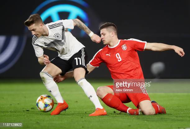Marco Reus of Germany and Luka Jovic of Serbia in action during the International Friendly match between Germany and Serbia at Volkswagen Arena on...