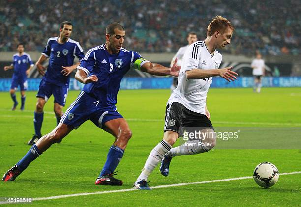 Marco Reus of Germany and Tal Ben Haim of Israel battle for the ball during the international friendly match between Germany and Israel at...