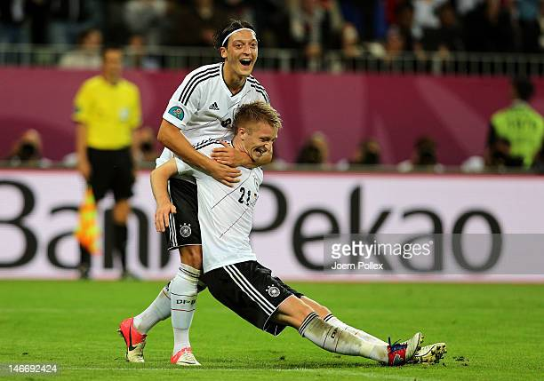 Marco Reus of Germany celebrates scoring their fourth goal with Mesut Ozil of Germany during the UEFA EURO 2012 quarter final match between Germany...