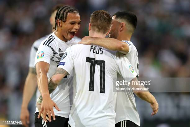 Marco Reus of Germany celebrates with teammate Leroy Sane and Ilkay Guendogan of Germany after scoring his team's fifth goal during the UEFA Euro...