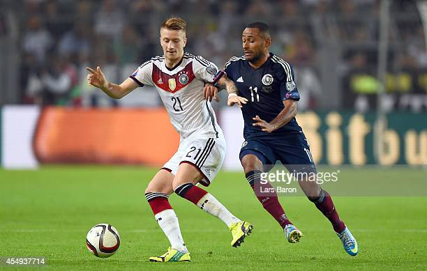 Marco Reus of Germany is challenged by Ikechi Anya of Scotland during the EURO 2016 Group D qualifying match between Germany and Scotland at Signal...