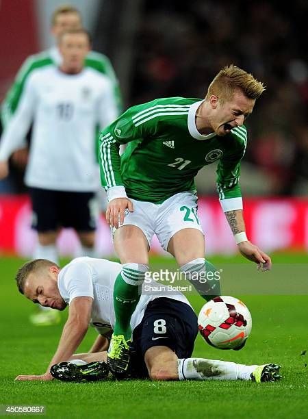 Marco Reus of Germany is tackled by Tom Cleverley of England during the international friendly match between England and Germany at Wembley Stadium...