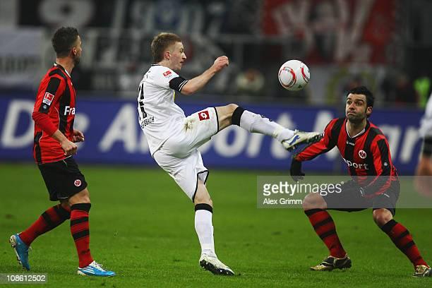 Marco Reus of M'Gladbach is challenged by Benjamin Koehler and Georgios Tzavellas of Frankfurt during the Bundesliga match between Eintracht...
