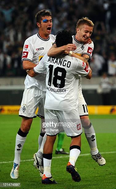 Marco Reus of Moenchengladbach celebrates with team mate Roman Neustaedter and Juan Arango after scoring his teams fifth goal against Michael Schulze...
