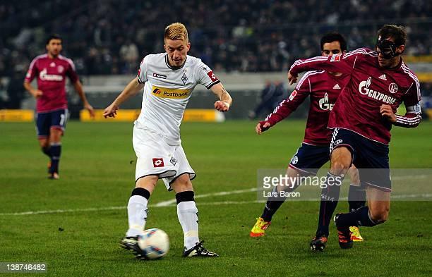 Marco Reus of Moenchengladbach scores his teams first goal next to Benedikt Hoewedes of Schalke during the Bundesliga match between Borussia...
