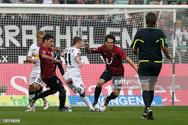 Marco Reus of Moenchengladbach scores the second goal against Karim Hagguio and Emanuel Pogatetz of Hannover during the Bundesliga match between...