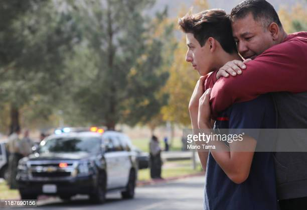 Marco Reynoso hugs his son 11thgrader Dylan Reynoso after reuniting at a park near Saugus High School after a shooting at the school left two...