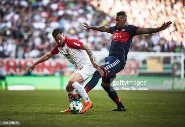 Marco Richter of Augsburg is challenged by Jerome Boateng of Bayern Munich during the Bundesliga match between FC Augsburg and FC Bayern Muenchen at...