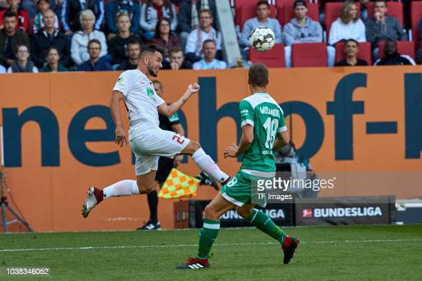 Marco Richter of FC Augsburg and Niklas Moisander of Werder Bremen battle for the ball during the Bundesliga match between FC Augsburg and SV Werder...