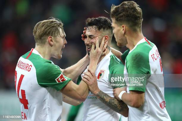 Marco Richter of FC Augsburg celebrates with teammates Fredrik Jensen and Florian Niederlechner after scoring his team's first goal during the...