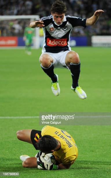 Marco Rojas of the Victory jumps over keeper Mark Birighitti of the Jets during the round 13 ALeague match between the Melbourne Victory and the...