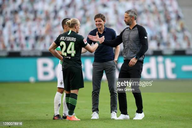 Marco Rose Head Coach of Borussia Moenchengladbach and Oliver Glasner Head Coach of VfL Wolfsburg shake hands with Xaver Schlager of VfL Wolfsburg...