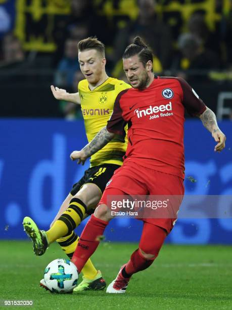 Marco Russ of Eintracht Frankfurt and Marco Reus of Borussia Dortmund compete for the ball during the Bundesliga match between Borussia Dortmund and...