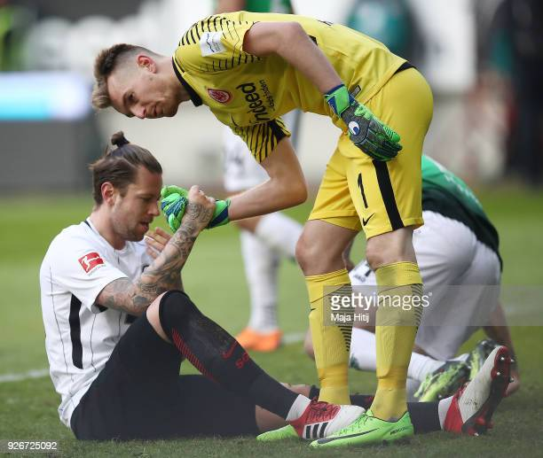 Marco Russ of Frankfurt is helped up by goalkeeper Lukas Hradecky of Frankfurt during the Bundesliga match between Eintracht Frankfurt and Hannover...