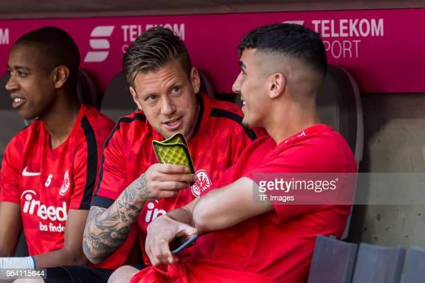 Marco Russ of Frankfurt speaks with Aymane Barkok of Frankfurt prior to the Bundesliga match between FC Bayern Muenchen and Eintracht Frankfurt at...