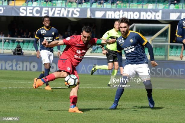 Marco Sau of Cagliari competes with Marco Ezio Fossati of Hellas Verona during the serie A match between Hellas Verona FC and Cagliari Calcio at...