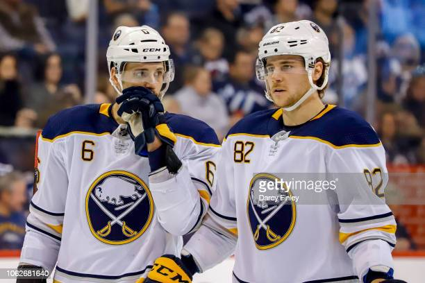 Marco Scandella and Nathan Beaulieu of the Buffalo Sabres discuss strategy during a second period stoppage in play against the Winnipeg Jets at the...