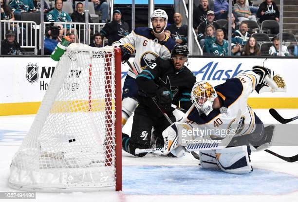 Marco Scandella of the Buffalo Sabres and Evander Kane of the San Jose Sharks watch the shot go past Carter Hutton of the Buffalo Sabres at SAP...