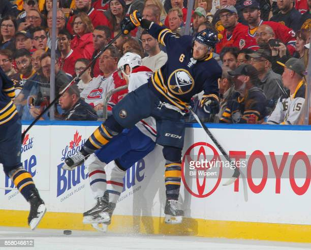 Marco Scandella of the Buffalo Sabres checks Ales Hemsky of the Montreal Canadiens during an NHL game on October 5 2017 at KeyBank Center in Buffalo...