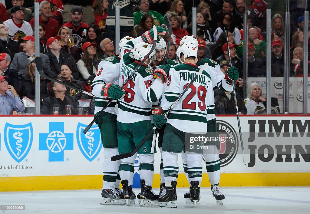 Marco Scandella #6 of the Minnesota Wild (middle) celebrates after scoring against the Chicago Blackhawks int he third period during the NHL game at the United Center on December 16, 2014 in Chicago, Illinois.