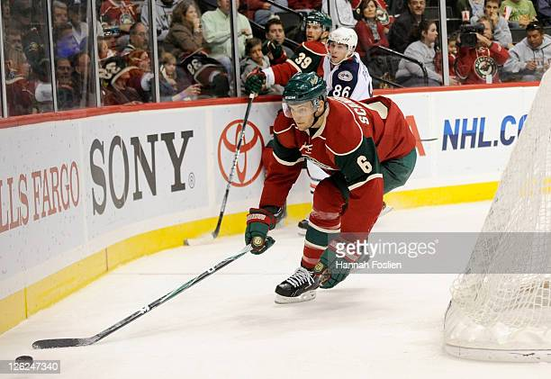 Marco Scandella of the Minnesota Wild handles the puck behind the net as Adam Payerl of the Columbus Blue Jackets checks Nate Prosser in the first...