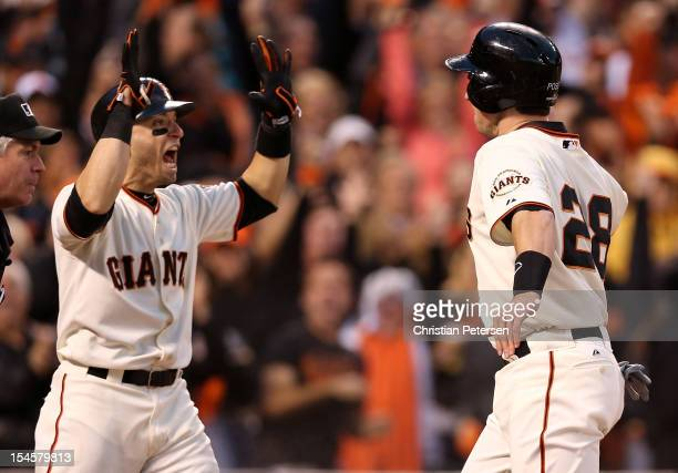 Marco Scutaro and Buster Posey of the San Francisco Giants celebrate after scoring in the third inning on a three-run double by Hunter Pence against...
