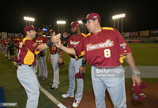 Marco Scutaro of Team Venezuela is greeted by manager Luis Sojo of Team Venezuela during player introductions before Pool C Game 1 between Dominican...